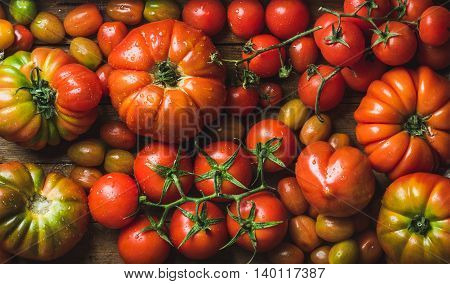 Colorful tomatoes of different sizes and kinds, top view, horizontal composition