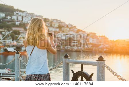 Young blond tourist woman making photo of sunset, harbour of Alanya, Mediterranean region, Turkey,