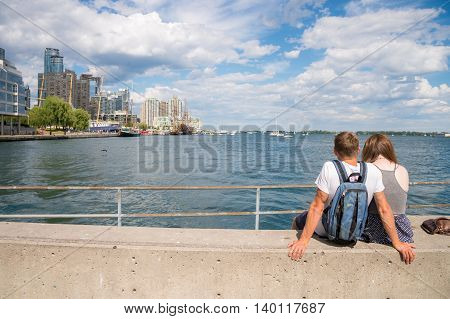 Toronto, Ca - 2 July 2016: Rear View Of A Young Couple Sitting On The Pier Looking At The Waterfront