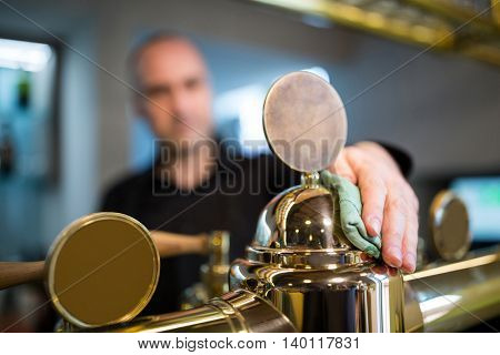 Close-up of bar tender cleaning beer pum at bar