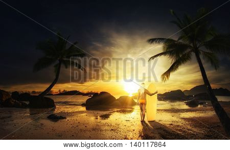 WOman with surfboard at the tropical  beach