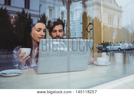 Young couple using laptop at coffee house