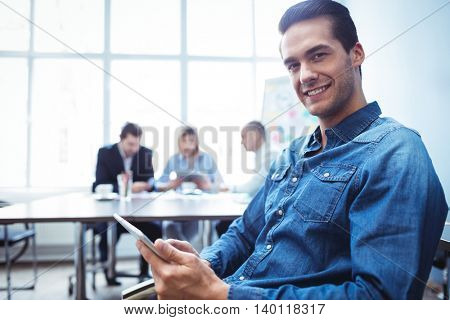 Portrait of smiling businessman using digital tablet against colleagues in meeting room at office
