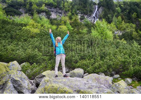 young woman in blue jacket on mountains slopes