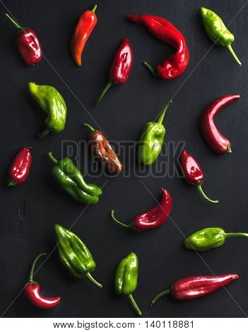 Pattern of small colorful hot chili peppers on black background, top view, vertical
