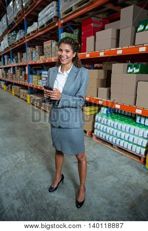 Business woman calling with someone in a warehouse