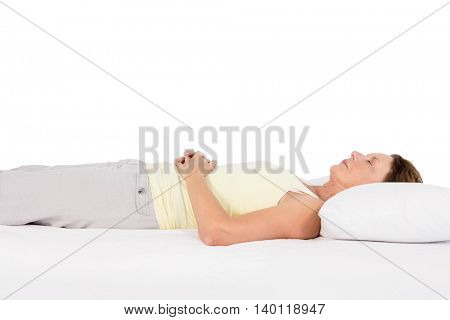 Mature woman sleeping on bed against white background