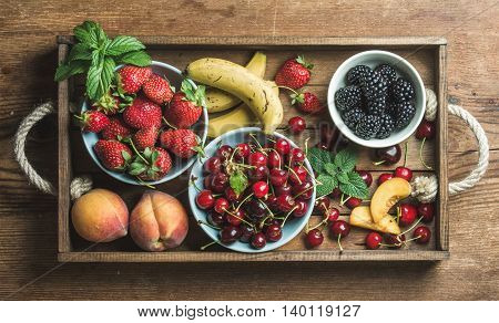 Summer fresh fruit and berry variety in rustic wooden tray over wooden backdrop, top view, horizontal composition