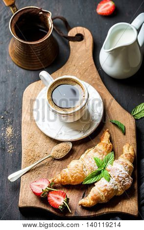 Breakfast set. Freshly baked croissants with strawberry, mint leaves and cup of coffee on wooden board served with pitcher and copper coffee pot over dark wooden backdrop, top view, selective focus