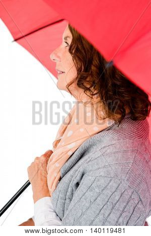 Thoughtful woman holding umbrella while standing against white background