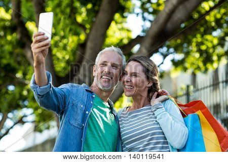 Happy mature couple taking selfie while holding shopping bags by tree