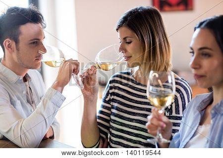 Young friends drinking wine by counter at restaurant