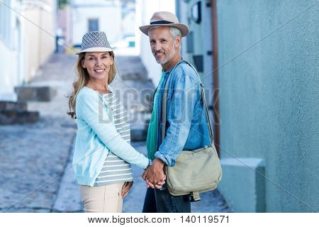 Portrait of smiling mature couple on street by building in city