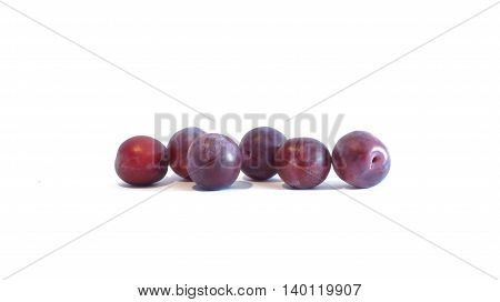 Ripe red plum lying on white background