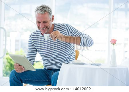Smiling mature man holding digital tablet while having coffee at restaurant