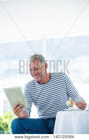 Happy mature man holding digital tablet while having food at restaurant