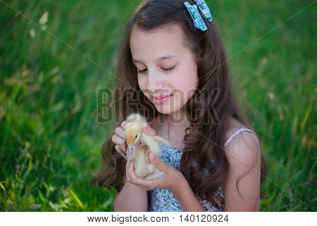 young girl with little yellow duckling in summer Park