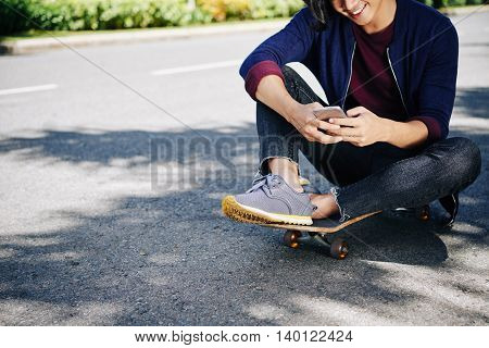 Cropped image of young man sitting on skateboard and texting