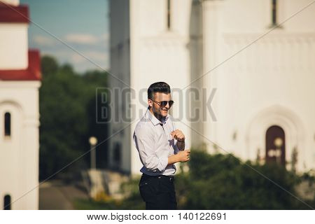 fashion portrait of a happy man in a white shirt and glasses