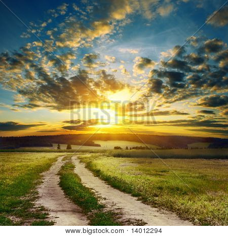 Road in field over sunset
