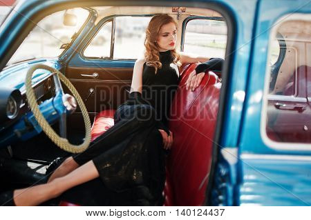 Portrait of beautiful sexy fashion girl model with bright makeup in retro style sitting in vintage car