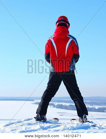 Skier standing on top of a hill before riding