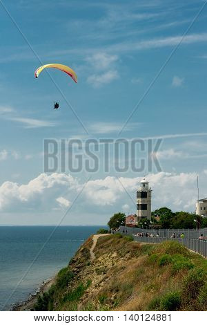 ride on a parachute over the sea near the mountains with a lighthouse