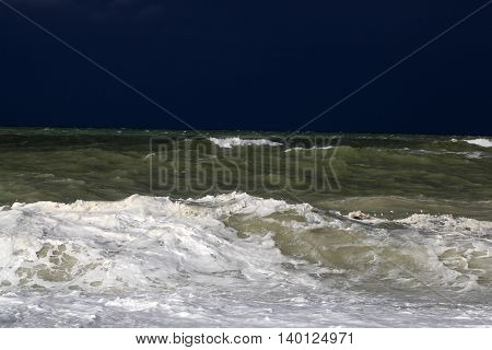 Stormy sea with waves und a dark blue sky.