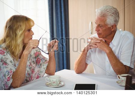 Senior couple discussing around a table around a coffee