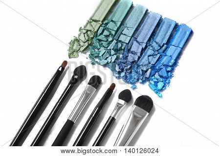 Smashed blue and green eye shadow palette with make up brushes isolated on a white background