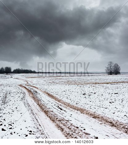 Rural road with snow and dark clouds