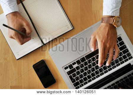 Young man's hand on top of the keyboard and with a pencil in notebook writes.