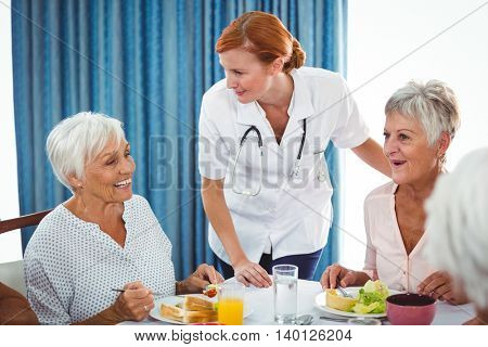 Smiling nurse looking at senior person during breakfast in a retirement home