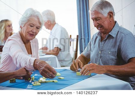 Senior persons enjoy playing domino on a table