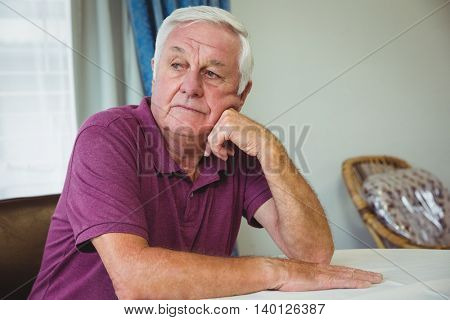 Senior man sitting at a table in a retirement home