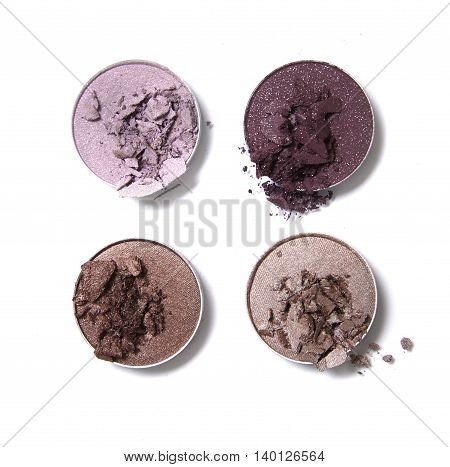Broken neutral and pink toned eye shadow make up pots isolated on a white background