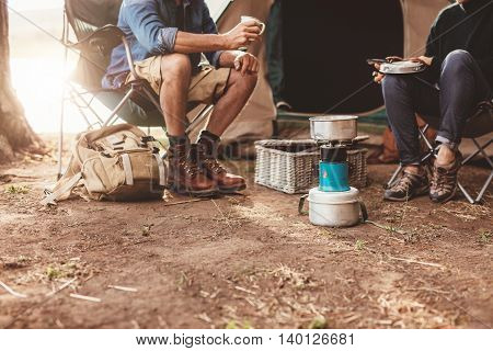 Cropped image of a couple sitting outside the tent and making coffee on a camp stove.