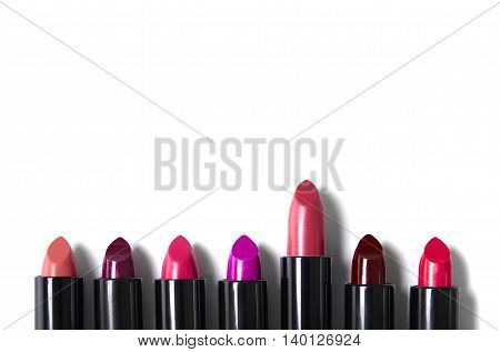 Lipsticks isolated on a white background and arranged to form a make up themed page footer