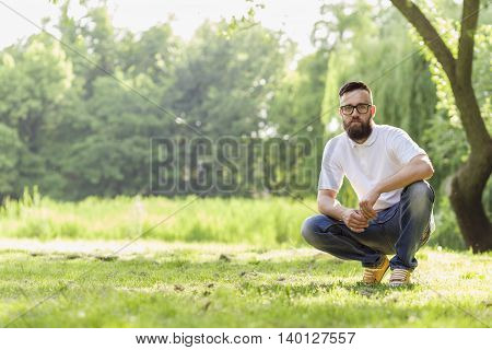 Man crouched down on the grass in a park enjoying a sunny day in nature