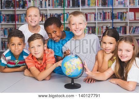 Portrait of school kids looking at globe in library at elementary school