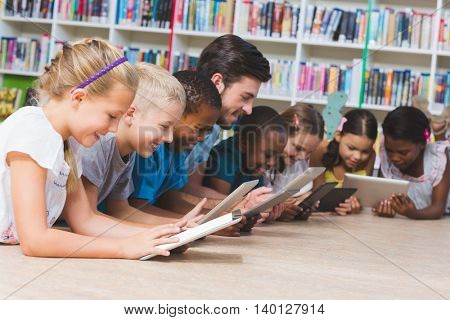 Teacher and kids lying on floor using digital tablet in library at elementary school