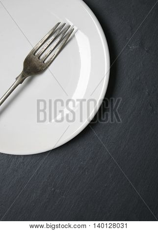 A silver fork with a white plate on a rustic slate background