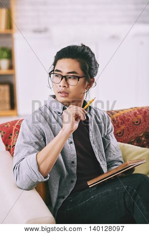 Portrait of stylish Vietnamese sketching in album