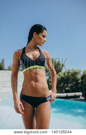 Female Model In Sports Wear Standing By The Poolside