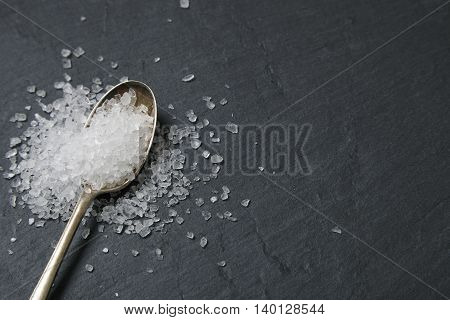 A spoon full of salt on a rustic slate background