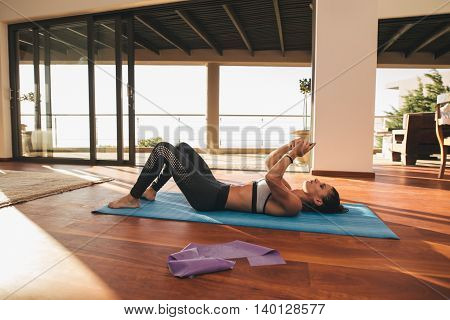 Fit Woman Lying On Exercise Mat With Cellphone
