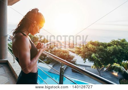 Fitness Woman In Balcony Using Mobile Phone