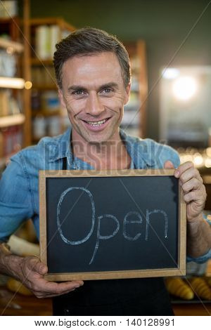 Portrait of a male staff holding a open sign in supermarket