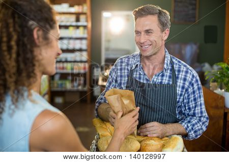 Smiling male staff giving packed bread to woman in supermarket