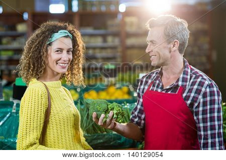 Smiling male staff assisting a woman with grocery shopping in supermarket